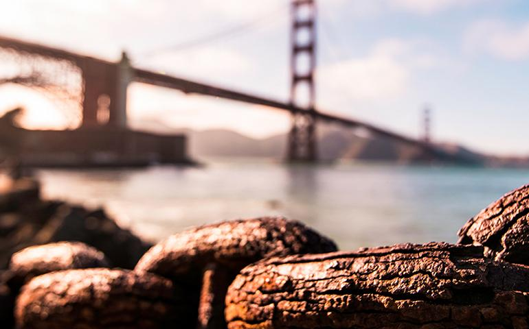 Image of large rusty tired old chains worn by weather along San Francisco Bay with the Golden Gate Bridge in the background.