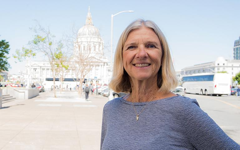 Retired female City & County of San Francisco employee standing in Civic Center with City Hall in the background.