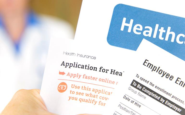 Stock image of a hand holding different enrollment and healthcare forms.