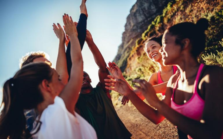 Photo of a group of women cheering and giving high fives outside on a trail.